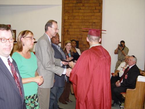 Chaplain Hughes awarding certificates at graduation